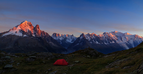Fotomurales - Red tent in the mountains near Chamonix, France, during a colorful sunset.