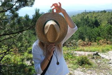 Blonde Frau mit Strohhut in der Natur