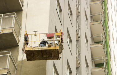 Facade finisher on the wall of high-rise building