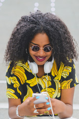 Afro-American woman in sunglasses using mobile with headphones around neck