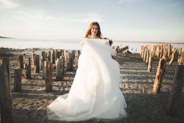 Pretty lady, bride posing in a wedding dress near sea on sunset