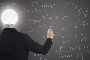businessman with lighbulb in head standing and hand drawing inspiration or idea, brainstorming on blackboard background.