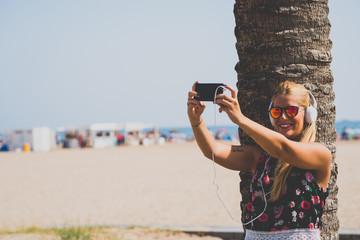 Smiling blonde girl makes selfie on beach