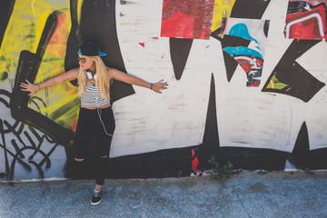 Beautiful woman in cap and headphones on graffiti wall