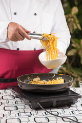 Chef fork over noodles by tongs