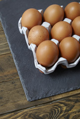 Chicken eggs on a rustic wooden background forming a page border