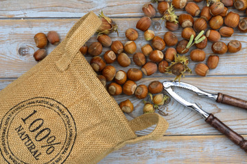 Organic hazel chest nuts in a 100% natural bag and nutcracker on a wooden background in vintage style