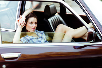 Brunette with long legs sitting in car , tinted photo