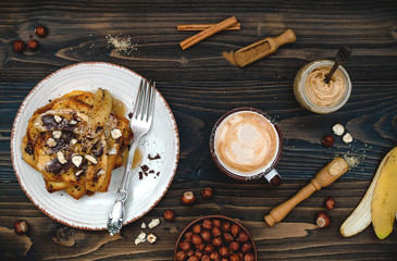 Healthy fall and winter breakfast. Vegan vanilla french toast with caramelized bananas, raw dark chocolate and hazelnut butter. Flat lay. Rustic country style. Ideal Christmas morning meal concept