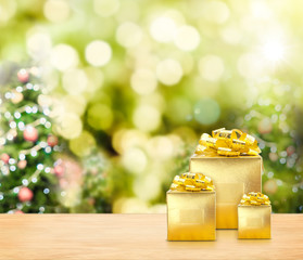 Golden presents on wood table top with christmas tree blurred bo