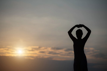 silhouette woman hand up in the sunset