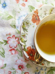 Overhead of tea in a floral cup and saucer on a flowery print fabric