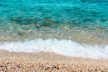Sea beach as background. Shells and clear blue water in tropical sunny day
