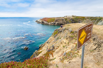 view of coastline from edge of cliff, danger sign in foreground