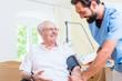 Krankenpfleger misst Blutdruck eines Patienten