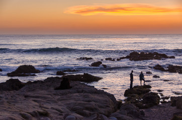 Ocean sunset with people standing on rocks