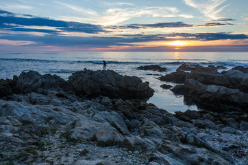 Lone person standing on rocks  with ocean sunset