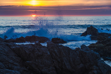waves crashing against rocks at sunset over the sea