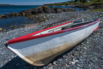 small wooden boat beached on shore