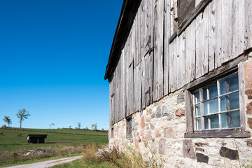 old stone foundation barn with blue sky in background