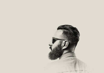 Black and white portrait of a Bearded Man in a denim shirt and glasses  on toned background. There is a spase for your text.