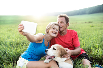 Senior runners with dog resting, taking selfie. Sunny nature.