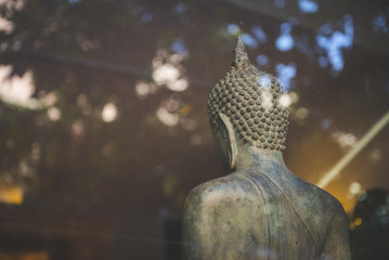 Image of buddha behind glass in vintage tone.