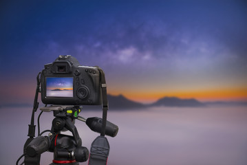 Closeup of a camera on a tripod outdoors taking photo of the sky