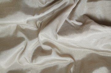 A full page of dark cream colored satin fabric texture