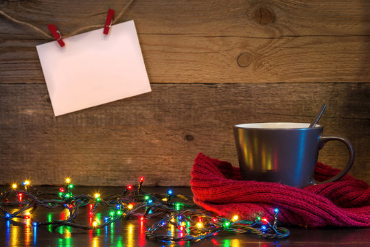 Christmas background with cup wrapped in red scarf and lights on