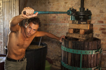 Young shirtless winemaker farmer working on a traditional wine press