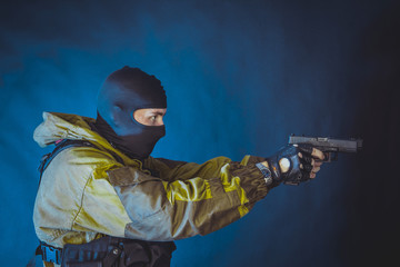 The man in the image of a member of the special forces division with two pistols in blue light. Russian police special force - Special Rapid Response Unit or SOBR (Spetsnaz).
