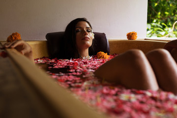 Woman relaxing in bath tub with flower petals at spa