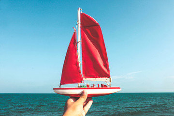 Toy red sailboat in hand on the background of sea and blue sky