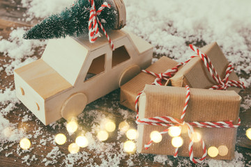 Wooden car carrying a pine tree next to the christmas gifts