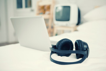 Black Headphones on the bed and laptop computer