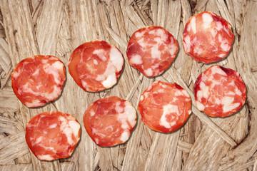 Pork Salami Slices On Wooden Chipboard Grunge Background