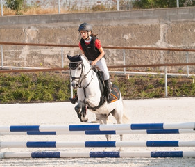 Girl with roan pony on showjumping competition