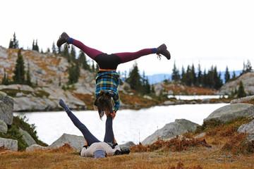 Two friends doing acro yoga, Kokanee Glacier Park, British Columbia, Canada