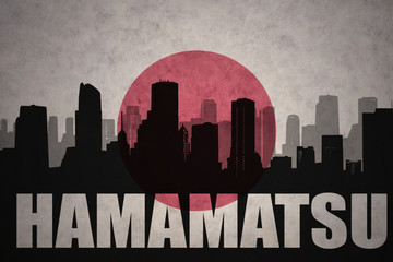 abstract silhouette of the city with text Hamamatsu at the vintage japanese flag background