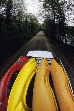 Van full of whitewater kayaks on backroad in Laurentien Mountains, Quebec, Canada.