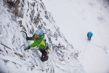A strong female ice climber works her way up Snowline WI4, Even Thomas Creek, Kananaskis, Alberta, Canada