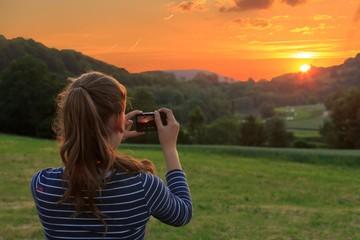 Mädchen fotografiert Sonnenuntergang