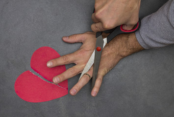 man cuts scissors finger with wedding ring