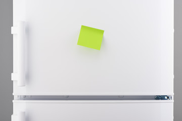 Blank green sticky paper note on white refrigerator
