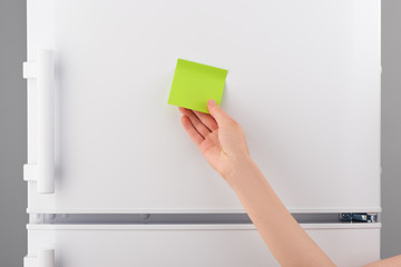 Female hand holding blank green paper note on white refrigerator