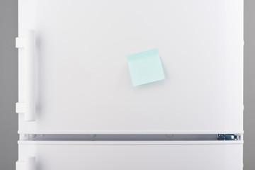 Blank light blue sticky paper note on white refrigerator