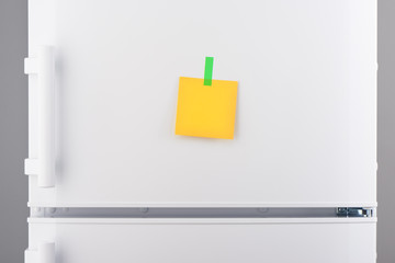 Blank yellow paper note and green sticker on white refrigerator
