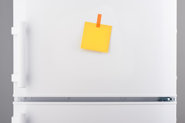 Blank yellow paper note and orange sticker on white refrigerator