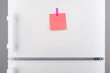 Blank pink paper note and pink sticker on white refrigerator